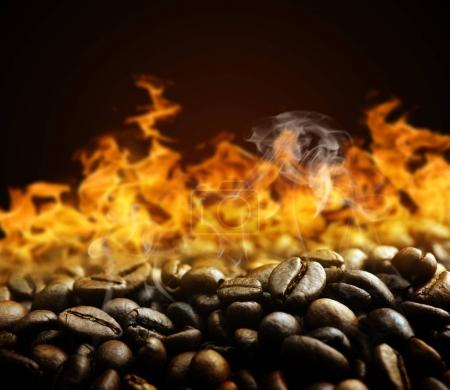 Roasted coffee beans with fire on the background.