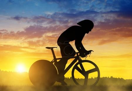 Silhouette of a cyclist on a road racing bike at sunset.