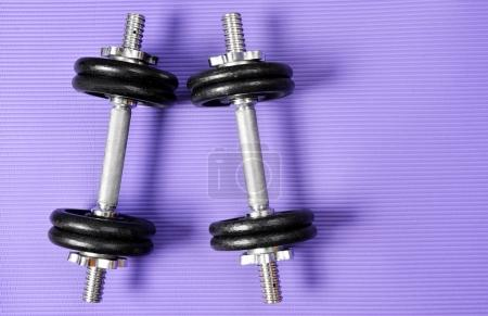 Black dumbbell on purple fitness mat. Exercise equipment. Healthy lifestyle concept.