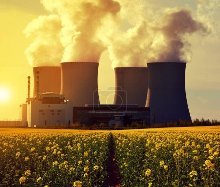 Nuclear power plant Temelin with rapeseed or canola field at sunrise - Czech Republic, Europe.
