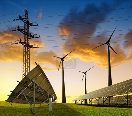 Foto de Turbinas eólicas con panel de energía solar y pilón de transmisión de electricidad en el campo contra la puesta del sol. Concepto de recursos sostenibles . - Imagen libre de derechos