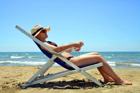 Girl lying on a sun lounger on sandy beach. Summer vacation by the sea.