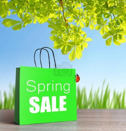 Green shopping bag with spring sale word on table.