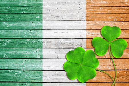 Green clover leaves or shamrocks on wooden background in the color of Irish flag.Saint Patricks day.