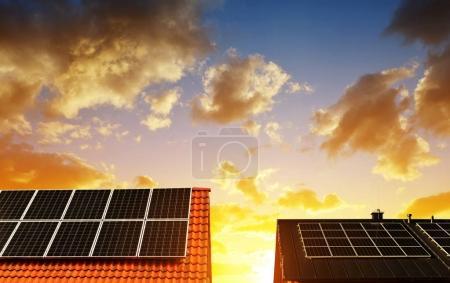 Foto de Panel de energía solar en el techo de la casa en el cielo del atardecer de fondo. El concepto de vivienda ecológica. - Imagen libre de derechos