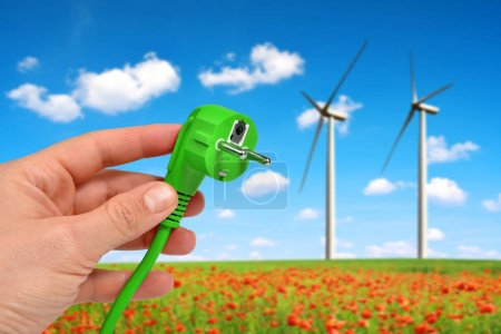 Hand holding green electric plug in the background wind turbines. Green energy concept.