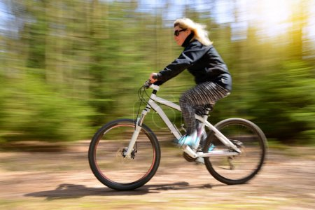 Woman riding a mountain bike on a forest path. Sport and active life concept. Motion blurred shot.