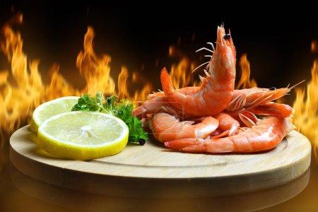 Photo pour Crevettes fraîches avec une tranche de citron sur carton à découper. - image libre de droit