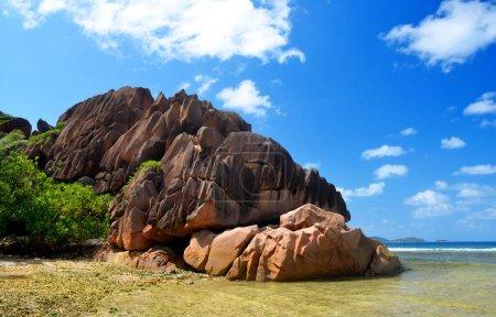 Foto de Isla de la Digue, Océano Índico, Seyshelles. Gran roca de granito en la playa de Anse Grosse Roche. Paisaje tropical con mar y cielo azul. - Imagen libre de derechos