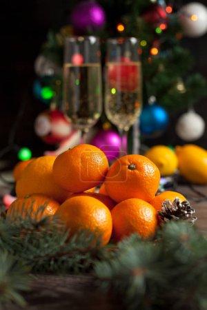 Photo pour Table traditionnelle du Nouvel An, mandarines, champagne, sapin de Noël et lumières du Nouvel An - image libre de droit