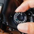 Постер, плакат: Program dial mode on dslr camera with fingers on the dial