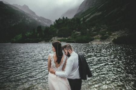 happy newlyweds on coast of mountain lake