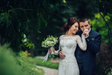 young attractive wedding couple, groom kissing hand of bride in park