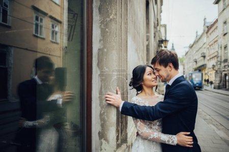 newly wedded couple posing near old shabby wall