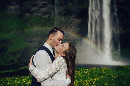 Photo pour Couple marié embrassant près d'une cascade le jour - image libre de droit