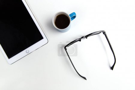 Photo for Glasses, coffee and tablet computer on white office desktop - Royalty Free Image