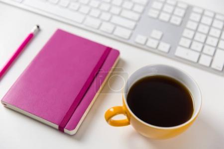 Photo pour Café, cahier, crayon et clavier d'ordinateur sur table de bureau blanche - image libre de droit