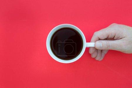 Foto de Mano que sujeta la taza de café encima de la cabeza sobre fondo rojo brillante - Imagen libre de derechos