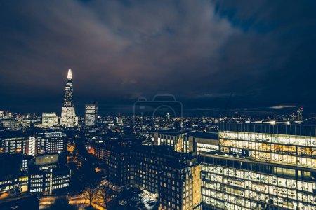 Photo pour Vue aérienne du paysage urbain des toits et des immeubles de bureaux sur les toits modernes de Londres la nuit - image libre de droit