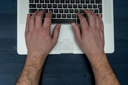 Overhead view of man typing on laptop computer keyboard desk