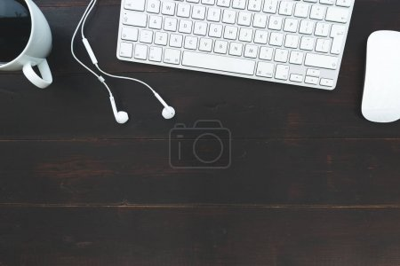 White computer keyboard mouse earphones and coffee cup overhead on dark brown table background
