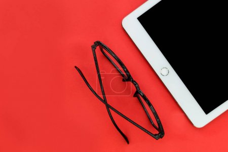 White tablet computer earphones and reading eyeglasses overhead on bright red background