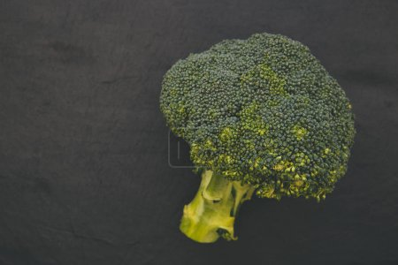 Raw broccoli isolated on dark background overhead with copy space