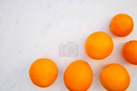 Bunch of oranges overhead on white marble background with copy space