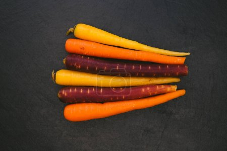 Top view of colorful carrots on dark background