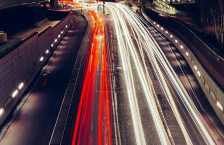 City light trails of fast moving car traffic on road in London at night