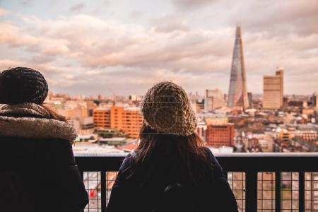 Photo pour Deux jeunes touristes en regardant les bâtiments modernes de skyline London nuageux - image libre de droit