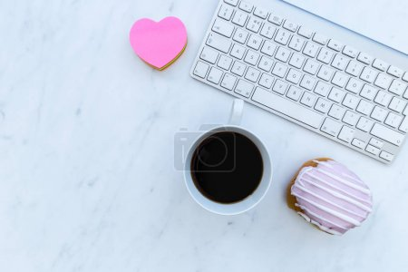 Computer keyboard, coffee, pastry and love heart on white marble background