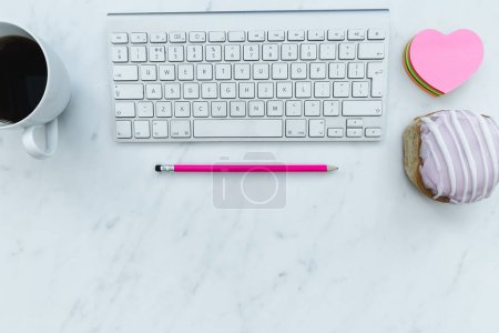 Photo for Computer keyboard, coffee, pastry and love heart on white marble background - Royalty Free Image