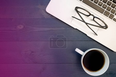 Laptop computer keyboard, eyeglasses and coffee