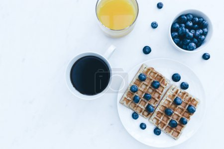 Waffles and blueberries with coffee and juice