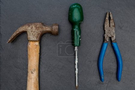 Old hammer screwdriver and pliers DIY tools on dark background