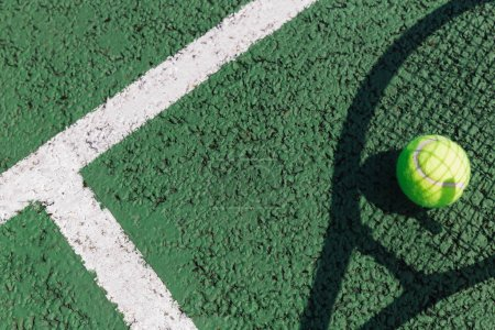 Tennis racket shadow and ball on green tennis court