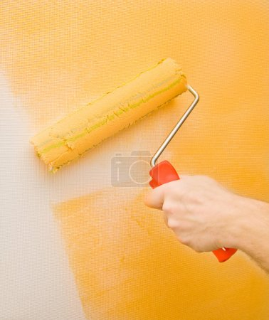 Photo pour Image d'une main peignant le mur avec un rouleau - image libre de droit