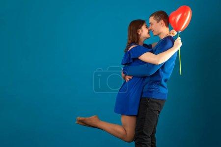 Photo pour Jeune couple amoureux sur fond bleu avec des ballons rouges. Saint Valentin - image libre de droit