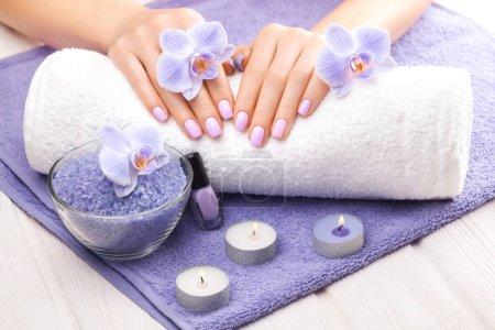 Photo pour Belle rose manucure avec décor, orchidée, serviette et bougie sur la table en bois blanche. spa - image libre de droit
