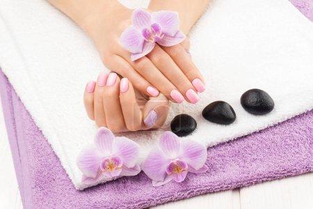 Photo pour Belle manucure rose avec décor, orchidée, serviette sur la table blanche en bois. spa - image libre de droit