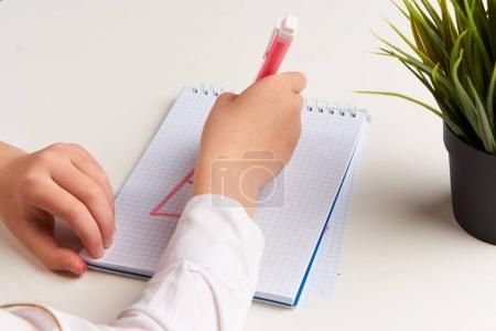 Photo pour Fille dessine avec sa main droite dans un carnet sur la table . - image libre de droit