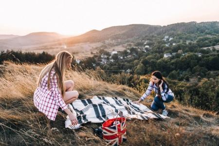 Beautiful girls on picnic in mountains