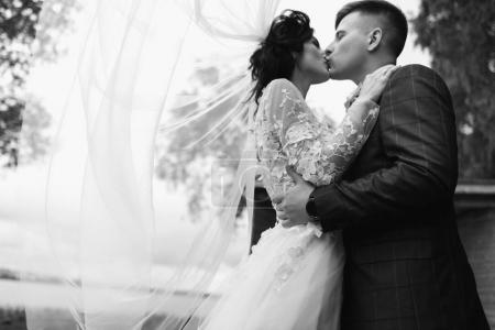 Happy young just married couple kissing at their wedding day