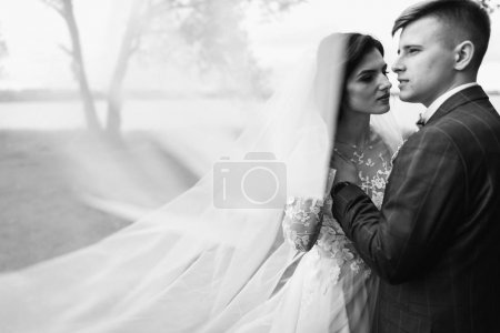 Happy young just married couple embracing at their wedding day