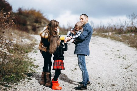 Photo for Family playing outside and father holding youngest daughter in hands - Royalty Free Image
