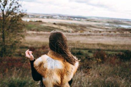 Rear view of woman wearing fur waistcoat outside