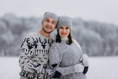 Portrait of romantic couple standing together in winter park