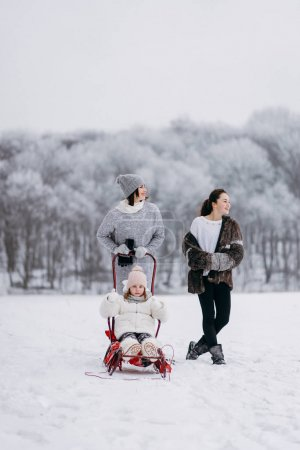 Mother with daughters walking in winter park and sledding smaller daughter