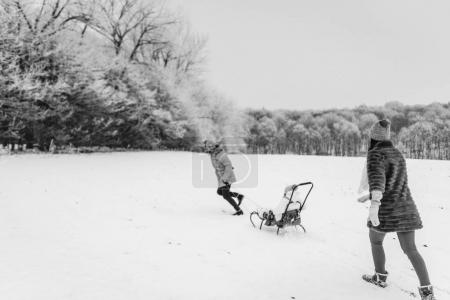 View of father sledding daughter and mother behind